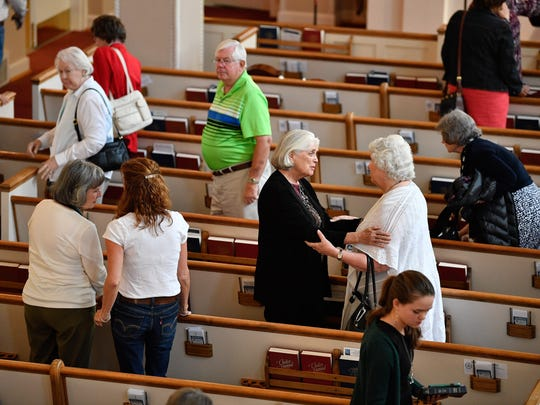 Parishioners greet each other following a service at
