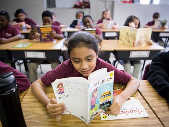 Third grader Milagro Moreno-Seda reads a book during independent reading at Nashville Classical Charter School in Nashville, Tenn., Wednesday, Dec. 13, 2017.