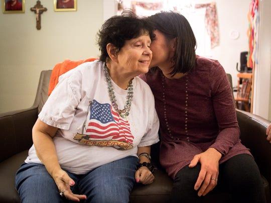 Volunteer Jenny Gustafson, right, kisses Jennifer Pettit