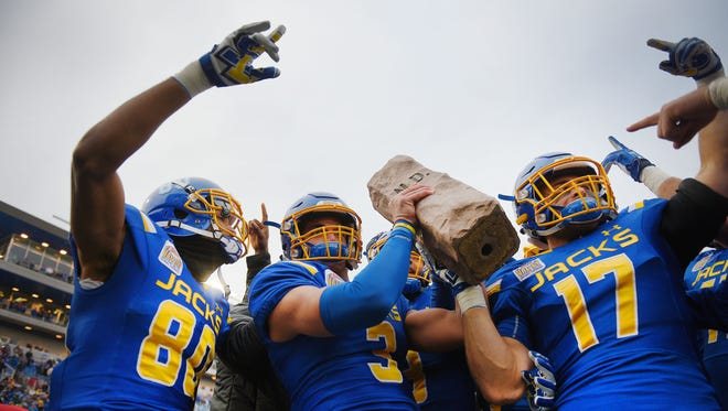 South Dakota State University's Adam Anderson, from left, Taryn Christion and Alex Romenesko hold the Dakota Marker up to the student section after their win over North Dakota State University in Brookings in 2017.
