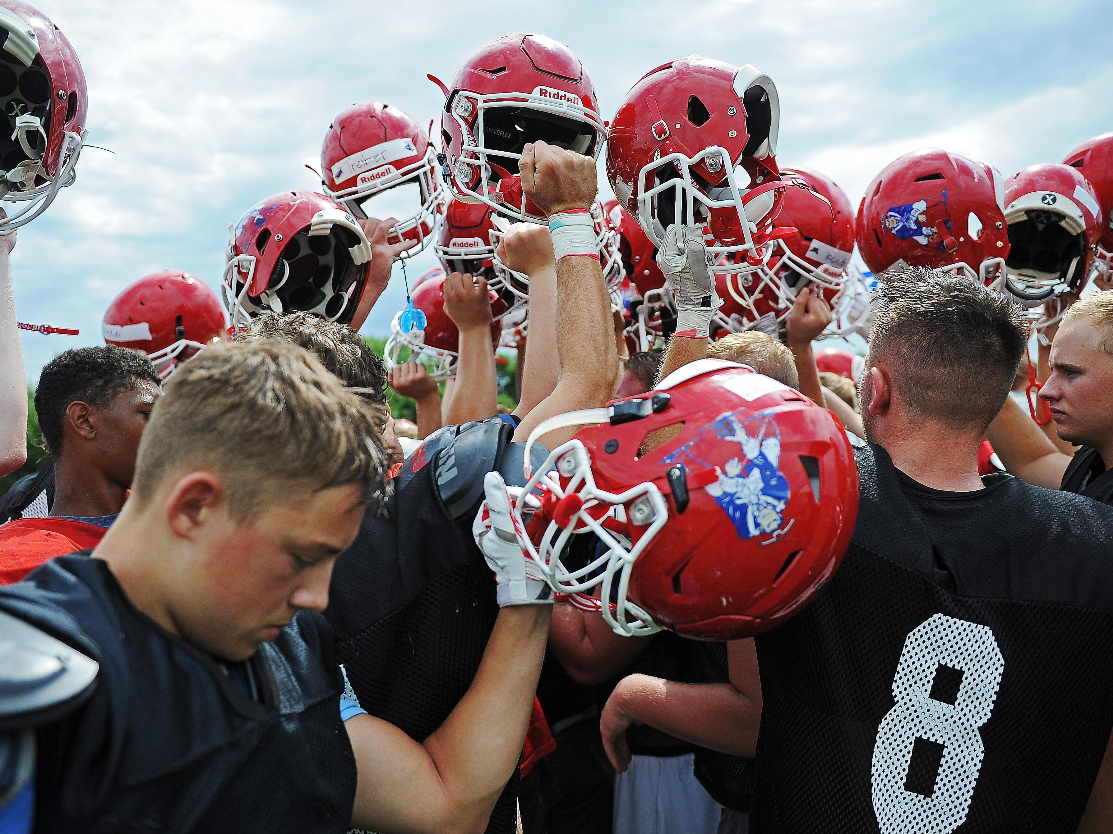 Lincoln High School football players huddle together at the end of a Lincoln High School football practice Thursday, Aug. 11, 2016, at Lincoln High School in Sioux Falls.