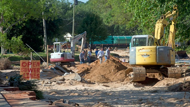 Utility crews inspect the damage to Piedmont Road Tuesday morning May 6, 2014. Last weekâ??s heavy rains and flood waters scoured out much of the roadway and severely damaged the underground utilities in the Cordova Park area.