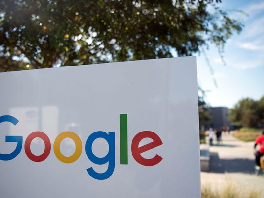 A man rides a bike past a Google sign and logo at the Googleplex in Menlo Park, California.