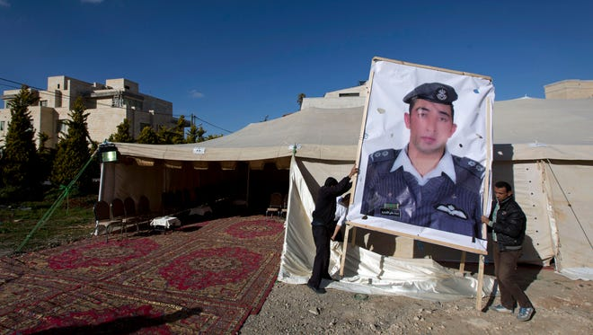A banner with a picture of Jordanian pilot Lt. Muath al-Kaseasbeh, who is held by Islamic State group militants, is hoisted by workers near a tent prepared for receiving supporters, in Amman, Jordan, Friday, Jan. 30, 2015.