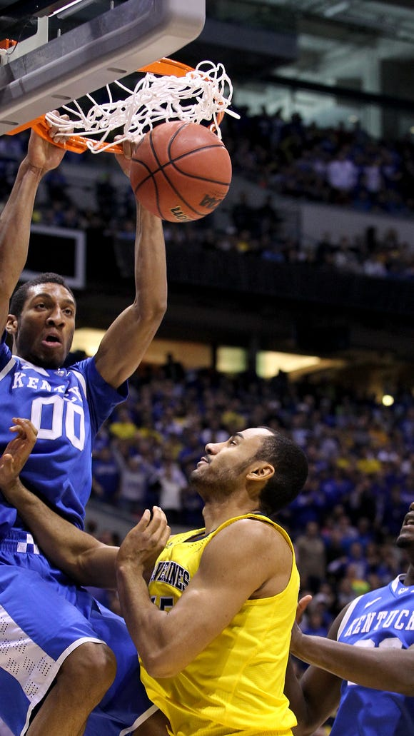 UK's Marcus Lee dunks over Michigan's Jon Horford during the Cats' Elite 8 game at the Lucas Oil Stadium in Indianapolis.