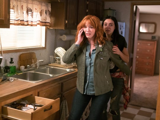 Cindy (Christina Hendricks, left) and her daughter, Kinsey (Bailee Madison), fight off uninvited guests in slasher thriller 'The Strangers: Prey at Night.'