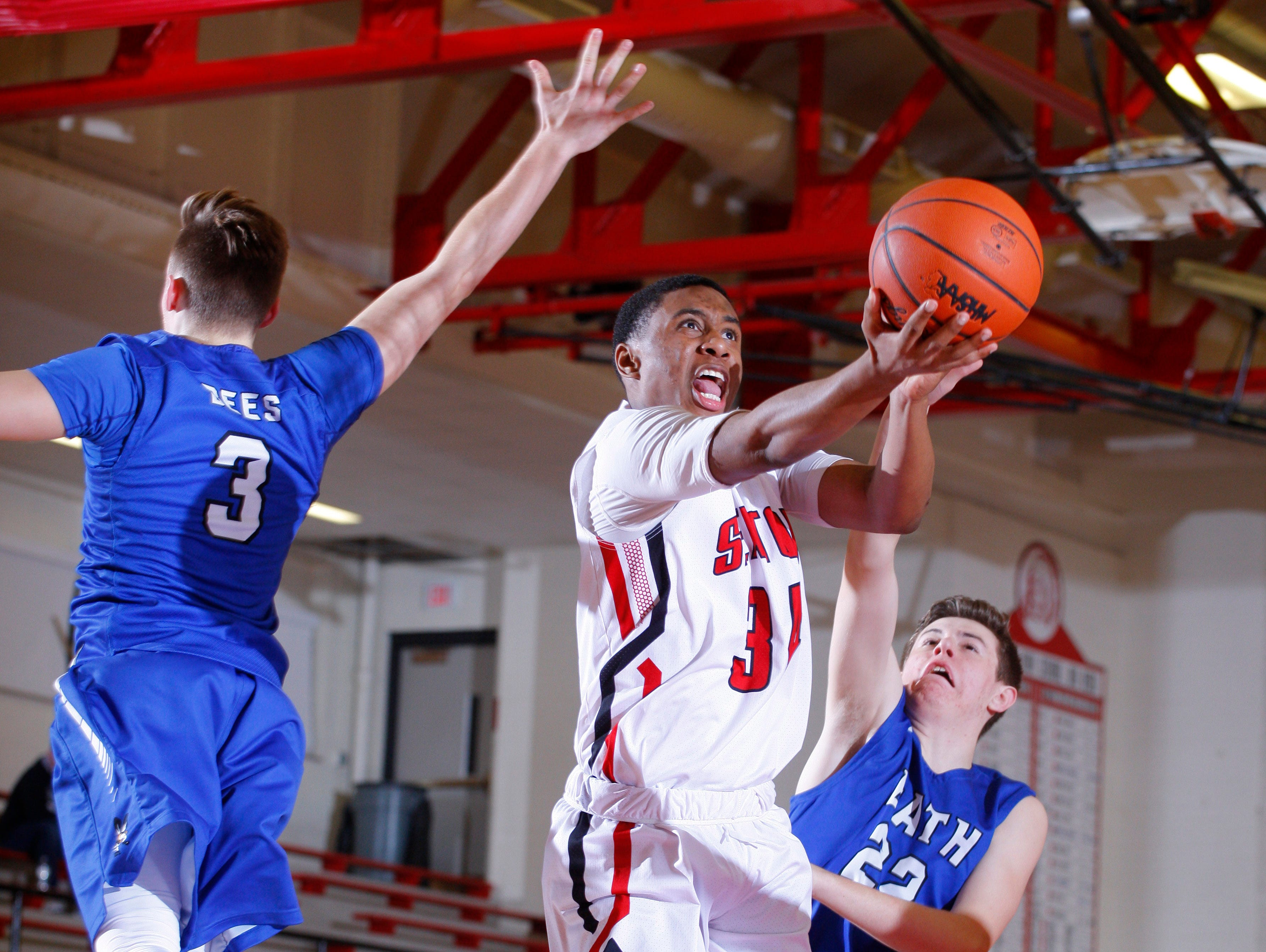 Sexton's Karl Brooks goes up for a layup between Bath's Max Tiraboschi, left, and Jacob Deveau, right, Tuesday, Feb. 7, 2017, in Lansing, Mich. Sexton won 82-39.