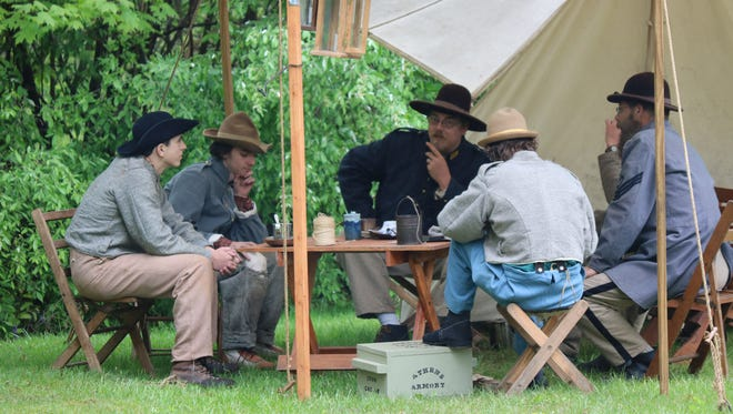 Re-enactors sit around the table under a tent near the battle encampment at the Civil War Days in Green Springs on Saturday morning.