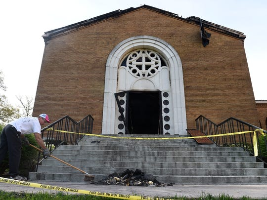 Kevin Clark sweeps away debris as cleanup continued at St. George Greek Orthodox Church on Kingston Pike on April 13, 2015. A fire gutted the inside of the church.