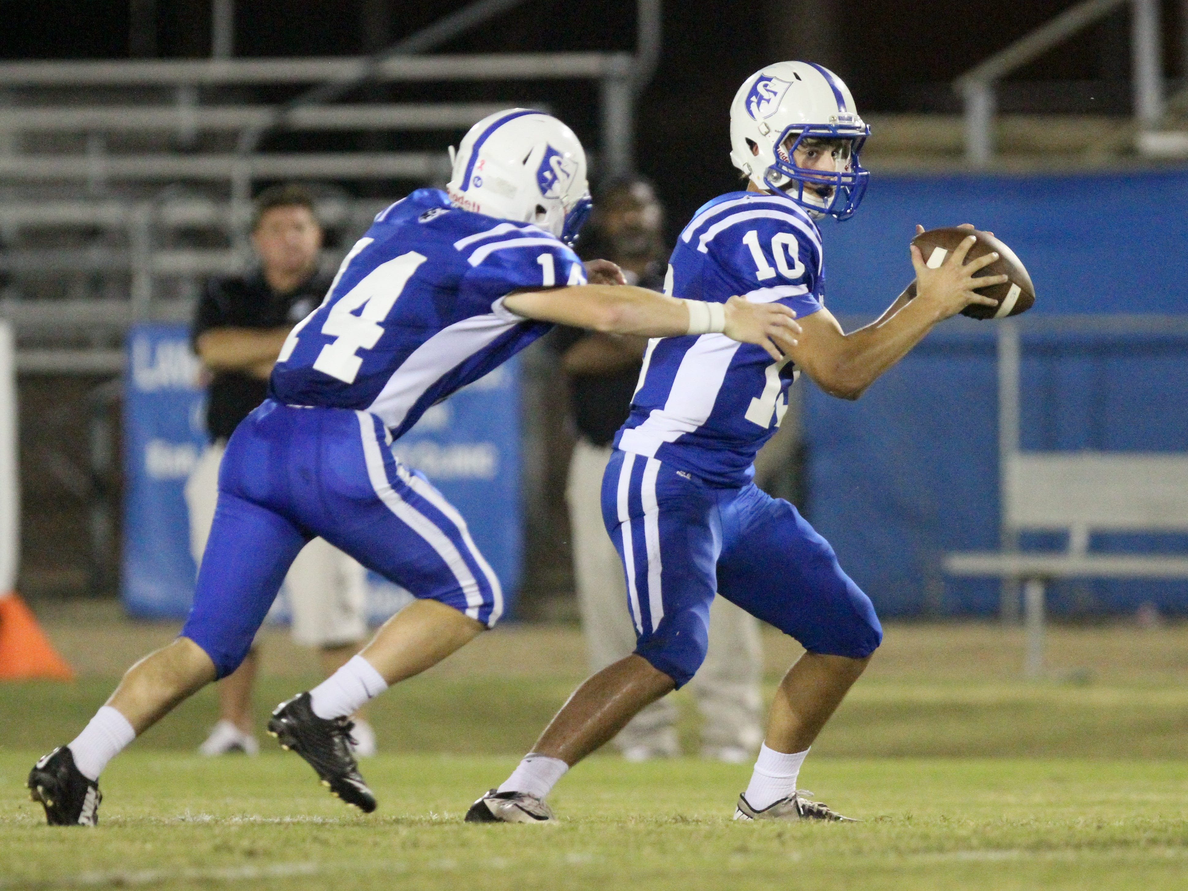 EMERALD MCINTYRE/THE NEWS-STAR St. Frederick quarterback Barrett Coon hands the ball to running back Jack Henry Turner against Tensas. The St. Frederick Warriors win their homecoming game against the Tensas Panthers, 47-12, Friday, Oct. 10, 2014, at Chip Luffey Field in Monroe, La.