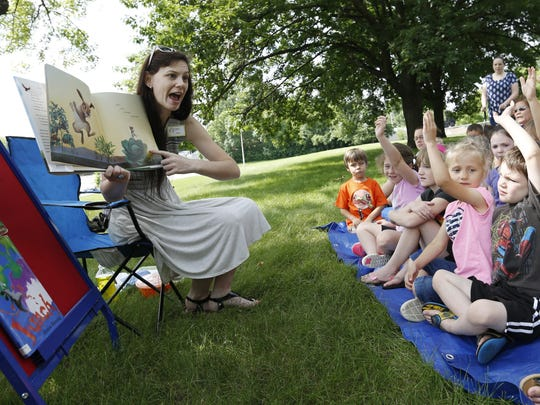 "Librarian Michelle Abrahamson (left) reads the children's book ""If You Plant a Seed"" and asks questions Thursday, June 18, 2015, during Sunshine Storytime at the South Side Library in Des Moines."