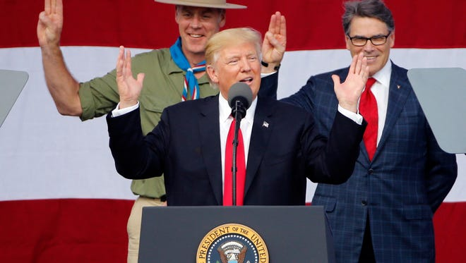 """FILE- In this Monday, July 24, 2017, file photo, President DonaldTrump, front left, gestures as former Boy Scouts Interior Secretary Ryan Zinke, left, and Energy Secretary Rick Perry watch at the 2017 National Boy Scout Jamboree at the Summit in Glen Jean, West Virginia. Boy Scouts president Randall Stephenson told The Associated Press on Wednesday, July 26, in his first public comments on the furor over President Donald Trump's speech on Monday that he'd be """"disingenuous"""" if he suggested he was surprised by the Republican president's comments. (AP Photo/Steve Helber, File)"""