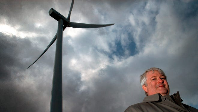 In this 2005 file photo, Bowling Green utilities director Daryl Stockburger poses under a wind turbine on the state's first wind farm just west of Bowling Green. Just two years after Ohio Gov. John Kasich championed a major rewrite of state energy policies, the Republican governor signed a sweeping bill in an election year that freezes phase-in of Ohio?s renewable energy and efficiency programs and repeals advanced energy goals altogether. (AP Photo/J.D. Pooley, File)