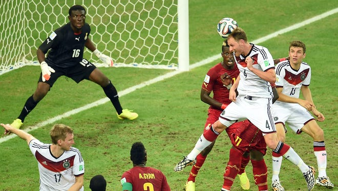Germany's Benedikt Hoewedes heads the ball toward Ghana's goal on Saturday in Fortaleza, Brazil. The World Cup Group G game ended in a 2-2 tie.