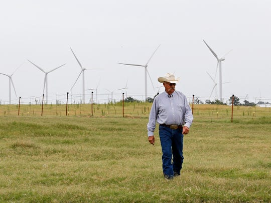 Rick Huffstutlar walks through a pasture at his home with wind turbines in the background in Calumet, Oklahoma.