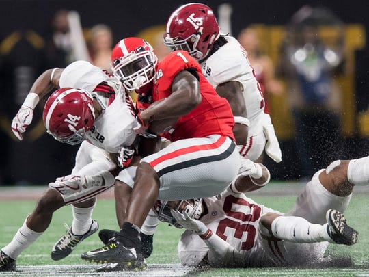 Georgia tailback Sony Michel (1) is stopped by Alabama defensive back Deionte Thompson (14) and linebacker Mack Wilson (30) in first half action of the College Football Playoff National Championship Game in the Mercedes Benz Stadium in Atlanta, Ga., on Monday January 8, 2018. (Mickey Welsh / Montgomery Advertiser)