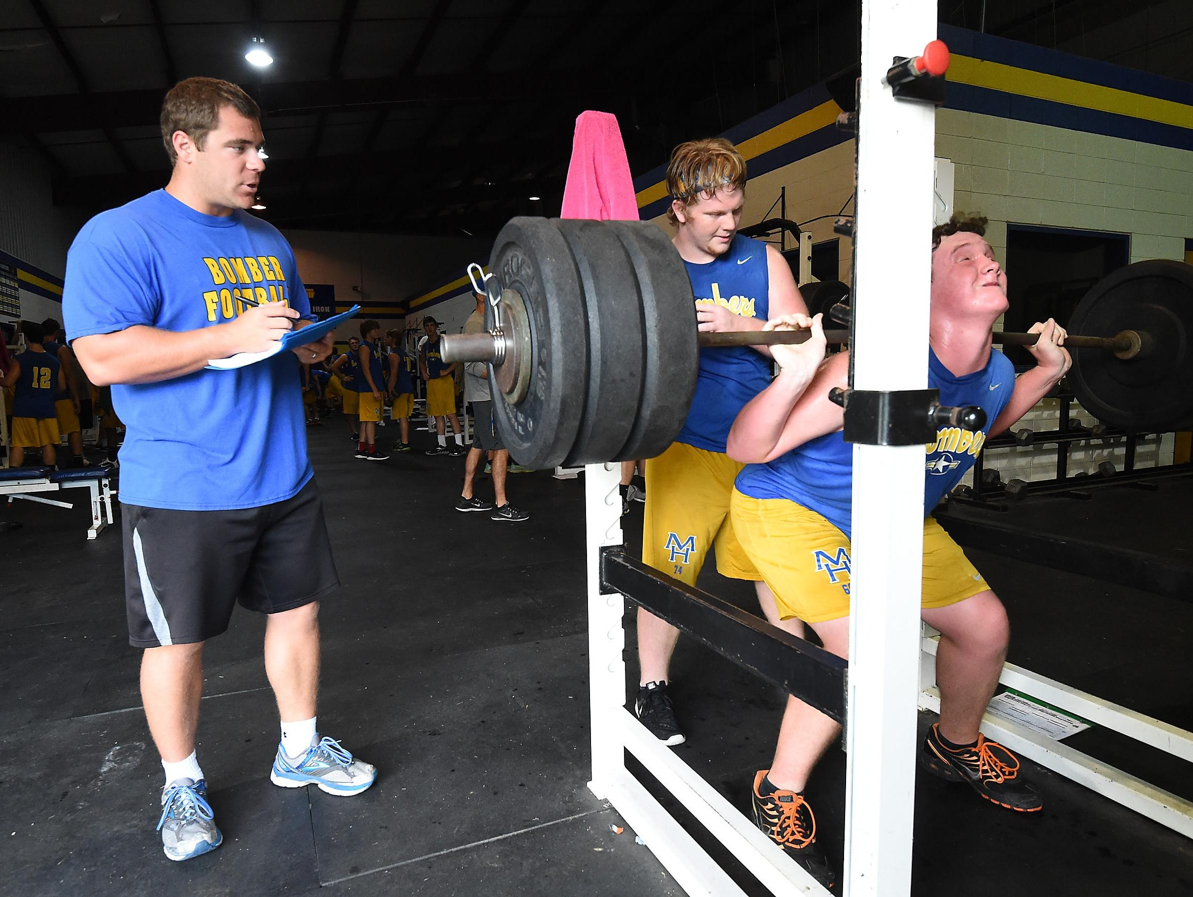Bomber assistant football coach Daniel Rodely, strength and conditioning coordinator, watches as John Fox performs squats Tuesday.