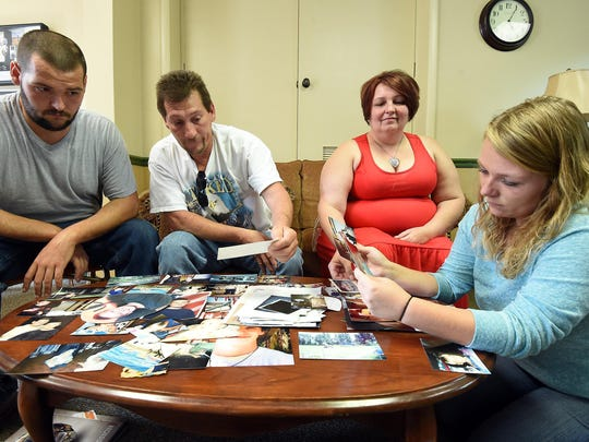 Michael McKenzie's family, from left, brother John McKenzie, father Johnny McKenzie, mother Deborah McKenzie and friend Jessica Miller, look at photographs of Michael while planning his funeral on Tuesday. Michael died after being struck by a car on Aug. 21.