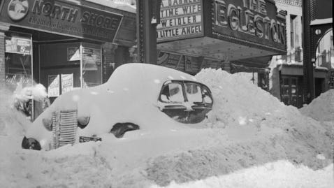 This car is buried in the snow outside The Egleston movie house. To learn more, visit the Jamaica Plain Historical at www.jphs.org. Photo from/www.jphs.org