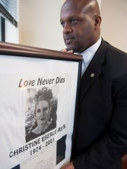 Former Philadelphia Eagle Ron Moten is now Deputy Chief at Camden County Prosecutor's Office. Here he holds a framed t-shirt given to him by the family of murder victim Christine Eberle. Monday, December 1, 2014.