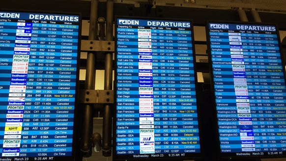 Departure boards at Denver International Airport show