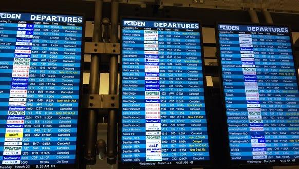Departure boards at Denver International Airport show