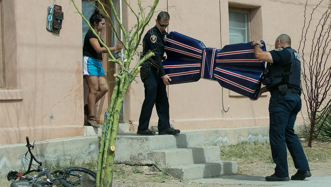 Las Cruces police officers William Gonzales, center, and Brian Gardea, right, remove the 6-foot by 3-foot Miguel Silva bow tie memorial from a home on the 700 block of E. May Street on Friday, March 4, 2016. The memorial was stolen from Klein Park earlier in March after it was hung on Feb 16, 2016, in the memory of former city councilor Miguel Silva.