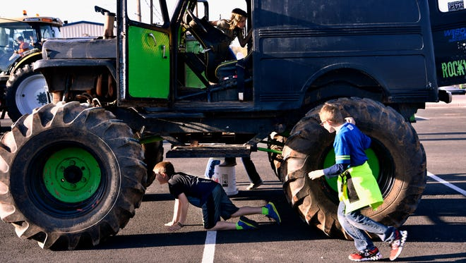 Children crawl beneath, into, and run around Joey Roland's monster truck Wednesday April 4, 2018 at Calvary Baptist Church in Snyder. Touch-A-Truck featured ten service vehicles for children in the church youth group to inspect up-close and interact with.