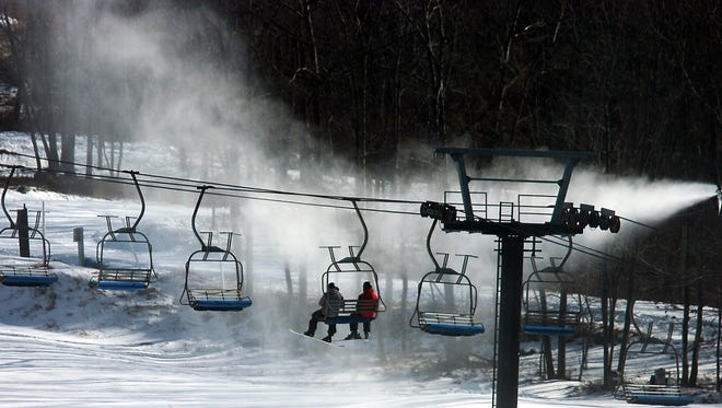 A few brave snowboarders ride up a ski lift during frigid temperatures Tuesday at Montage Mountain in Scranton, Pa. Few people were on the mountain because of temperatures dipping to -4 below zero.