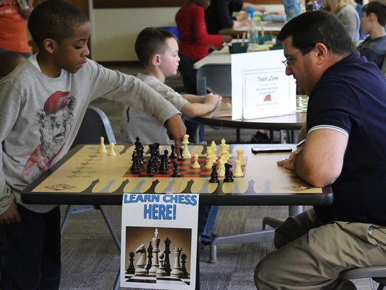 Elijah Wesley, 8, learns how to play chess from Raymond