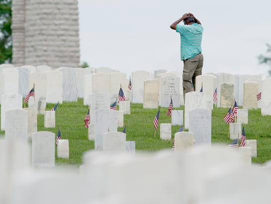 A man visits a grave at the Knoxville National Cemetery