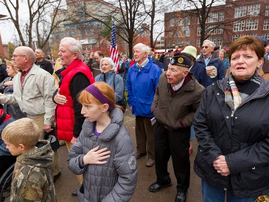 The crowd of more than 200 recite the Pledge of Allegiance