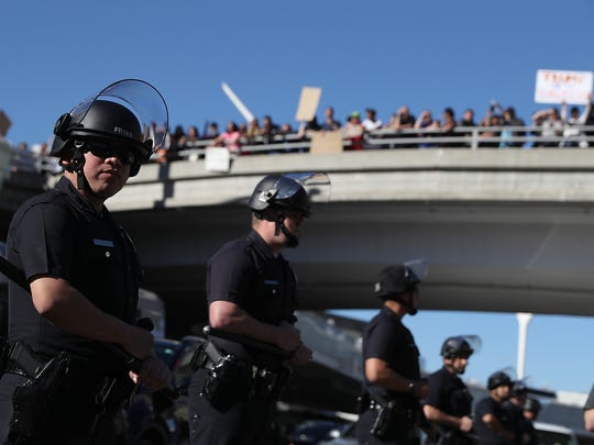 Los Angeles police officers monitor protesters during a demonstration against the travel ban that was imposed by President Trump at Los Angeles International Airport on January 29, 2017.