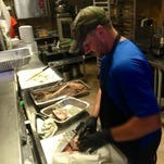 Chef-owner Reuben Sliva works to prep takeout orders during a busy lunch shift at Reuben's Smokehouse in southern Fort Myers Tuesday. In May the travel site TripAdvisor named Reuben's the No. 4 barbecue joint in the country, and crowds have packed this place since.