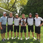 Coach Dan Young (far left) and the Plymouth Wildcats celebrate Thursday after winning the Division 1 varsity boys golf district at Fox Hills.