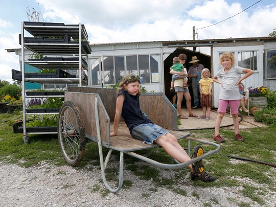 Abigail Schiebout, 8, sits in a cart chewing on the