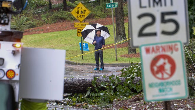 A man  looks at damage near her home on Tuesday, September 12. Georgia Power trucks were working to restore power for the neighborhood. Power was out for about 300,000 customers in four Atlanta Metro counties.