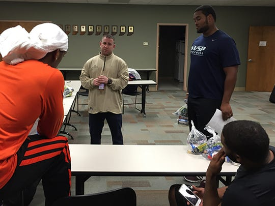 "Indianapolis sports agent Andrew ""Buddy"" Baker talks with client Leterrius Walton, at Baker's left, a defensive tackle from Central Michigan, and others training at St. Vincent Sports Performance. The bags are samples of healthy snacks and performance drinks."