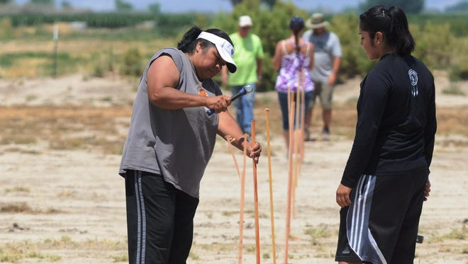 Mayleen Sam, left, pounds in a stake that will hold signs identifying where some campsites are at the Night in the Country music festival while other volunteers also work at the 2014 Boys & Girls Club of Mason Valley fundraising event.