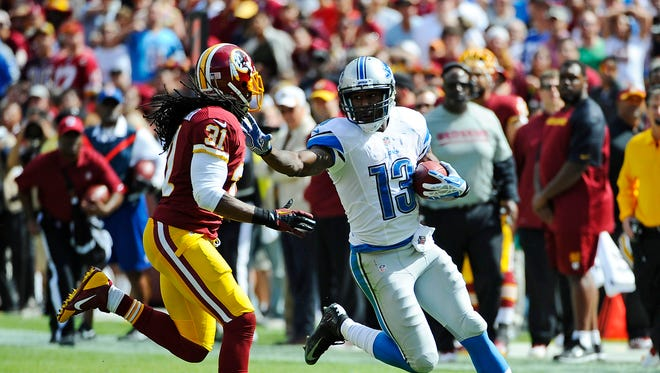 Detroit Lions wide receiver Nate Burleson (13) runs with ball as Washington Redskins safety Brandon Meriweather (31) defends during the first half at FedEX Field.