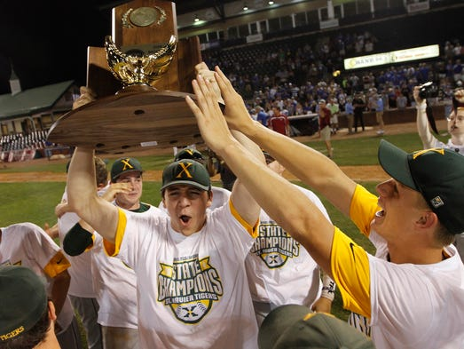 "Bryan ""Austin"" Clemons, left, hoists the trophy after St. X's 5-2 win over Simon Kenton in the championship game of the KHSAA State Baseball tournament in Lexington.  June 7, 2014"