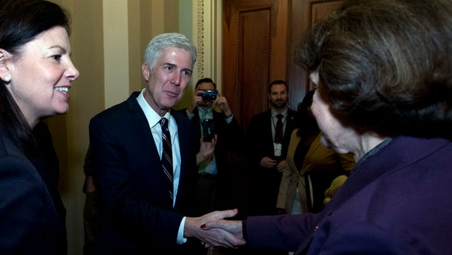 Supreme Court Justice nominee Neil Gorsuch, accompanied by former New Hampshire Sen. Kelly Ayotte, left, shakes hands with Sen. Dianne Feinstein D-Calif., ranking member of the Senate Judiciary Committee, on Capitol Hill in Washington on  Wednesday.