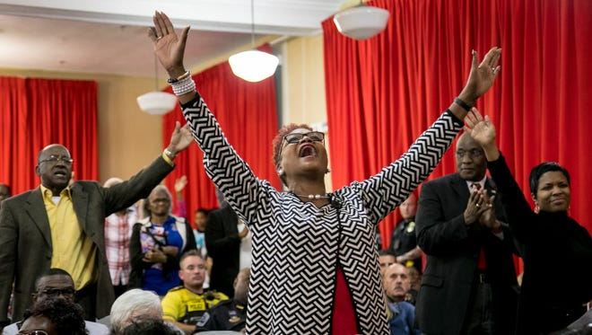 Windy Gavin lifts her hands in praise as two dancers from the Daughters of the King Praise Dance Ministry perform on Tuesday at the 8th Annual Community Prayer Service at the Dunbar Community School in Fort Myers.