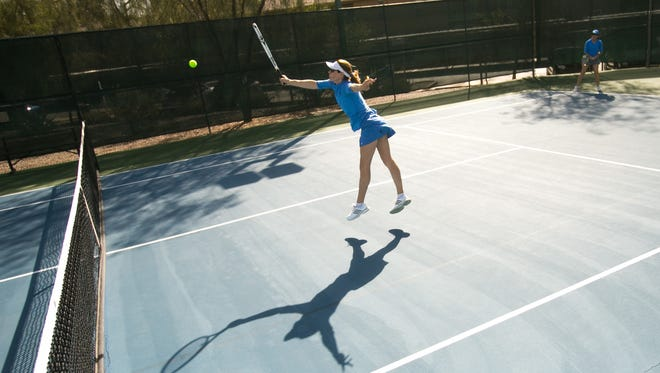 The city is proposing hourly fees to play tennis at Scottsdale Ranch Park and Indian School Park and Tennis Center, where Nikki Black delivers a forehand shot during a recent game.