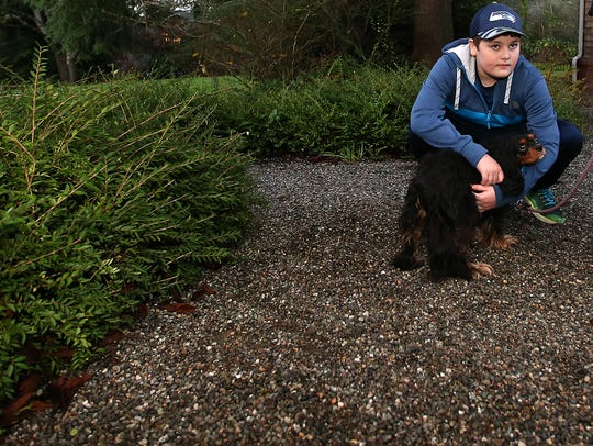 Charlie Odermat, 12, kneels down to hug his dog Skyla as he and his mother Regina Bellody talk about the recent wild animal attack that killed one of their dogs and chased Charlie and Skyla back into their Bainbridge Island house, on Tuesday, December 5, 2017.