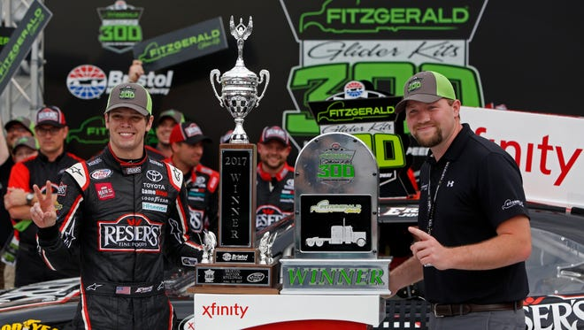 Driver Erik Jones, left, accepts the trophy after winning the NASCAR Xfinity Series race on Saturday.