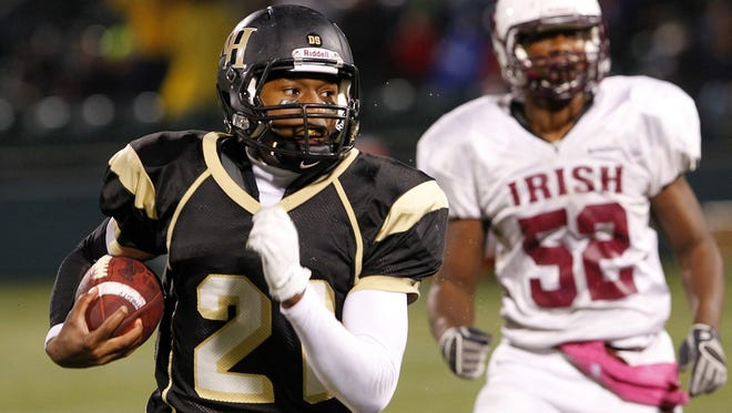 File photo 2012: R-H's Chauncey Scissum, left, runs the ball away during Section V Class AA semifinal football action between the Rush-Henrietta Royal Comets and the Aquinas Little Irish at Sahlen's Stadium in Rochester Sunday evening, October 28, 2012.