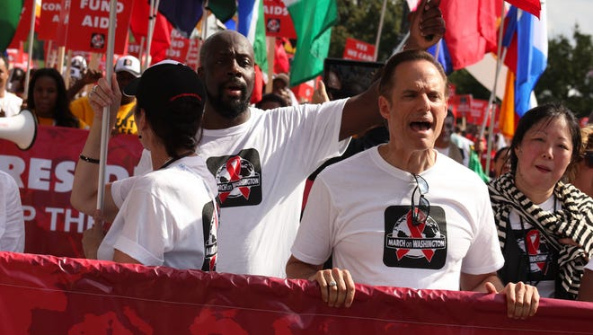 AIDS Healthcare Foundation President Michael Weinstein, center, marches in Washington, D.C., with comedian Margaret Cho, right, and musician Wyclef Jean, in July 2012.