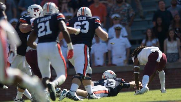 Auburn Tigers quarterback Sean White (13) fumbles the