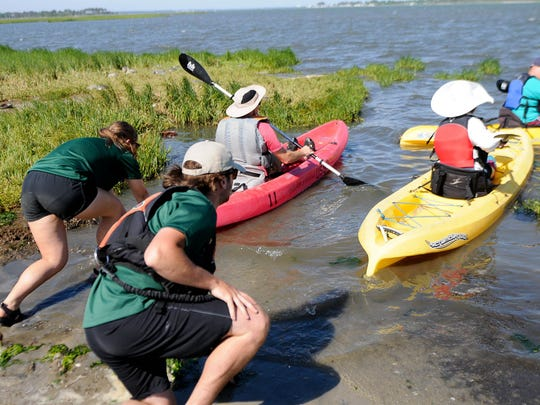 Casey Brotman and Andrew Kleinstauver, Delaware State Park tour guides, help push  kayakers into Rehoboth bay for an eco-tour around Delaware Seashore State Park. Tours are held throughout the summer.